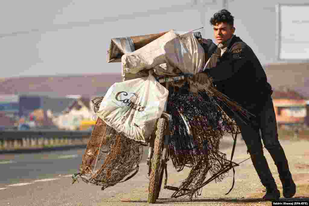 A Romany boy pushes a bicycle filled with iron scrap near the town of Obilic, Kosovo. (epa-EFE/Valdrin Xhema)