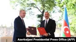 Turkish President Tayyip Erdogan (L) and Azerbaijani President Ilham Aliyev attend a signing ceremony in Shusha, in Nagorno-Karabakh, June 15, 2021.