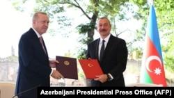 Turkish President Recep Tayyip Erdogan (left) and Azerbaijani President Ilham Aliyev attend a signing ceremony in Susa/Shushi in Nagorno-Karabakh on June 15.