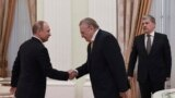 Russia -- Vladimir Putin, left, meets with opposition candidates shaking hands with Vladimir Zhirinovsky and with Pavel Grudinin,