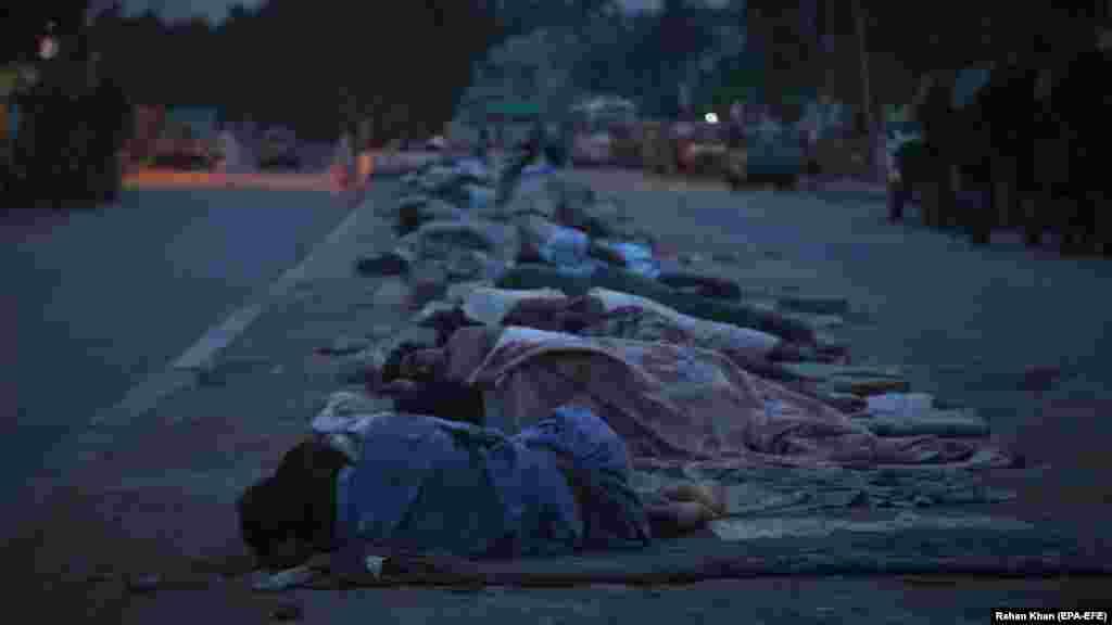 Бездомные спят на обочине дороги в Карачи, Пакистан