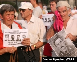 """Protesters hold pictures of victims and a poster reading """"Demand international investigation of missing cases!"""" at a rally in the center of Minsk on August 17."""