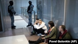 Employees of Aleksei Navalny's Anti-Corruption Foundation sit on the floor as security officers stand guard a raid on their office in Moscow in November 2020.