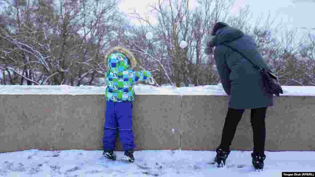 Мама з дитиною ліплять фігурки зі снігу на парапеті оглядового майданчика