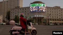 Қытай президенті Си Цзиньпин көрсетіліп жатқан көшедегі үлкен монитордың тұсынан өтіп бара жатқан мотоцикль мінген адам. Хотан, Шыңжаң, Қытай, 30 сәуір 2021 жыл.