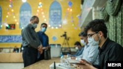 Iran -- Two Iranian voters are waiting to cast their ballots in the semi election of parliament, 2020.