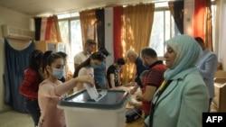 Një grua duke votuar të mërkurën në Alepo.