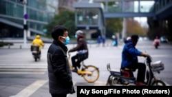 Люди на улице в китайском городе Ухань, где в конце 2019 года впервые был выявлен коронавирус.
