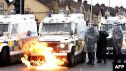 Violențele dintre autoritățile britanice și localnicii din zonă continuă în ciuda Acordului din Vinerea Mare, semnat în 1998. În această fotografie, flăcările cuprind un vehicul al poliției britanice, în timp ce ofițerii sunt atacați de tinerii naționaliști pe strada Springfield din Belfast, 8 aprilie 2021.