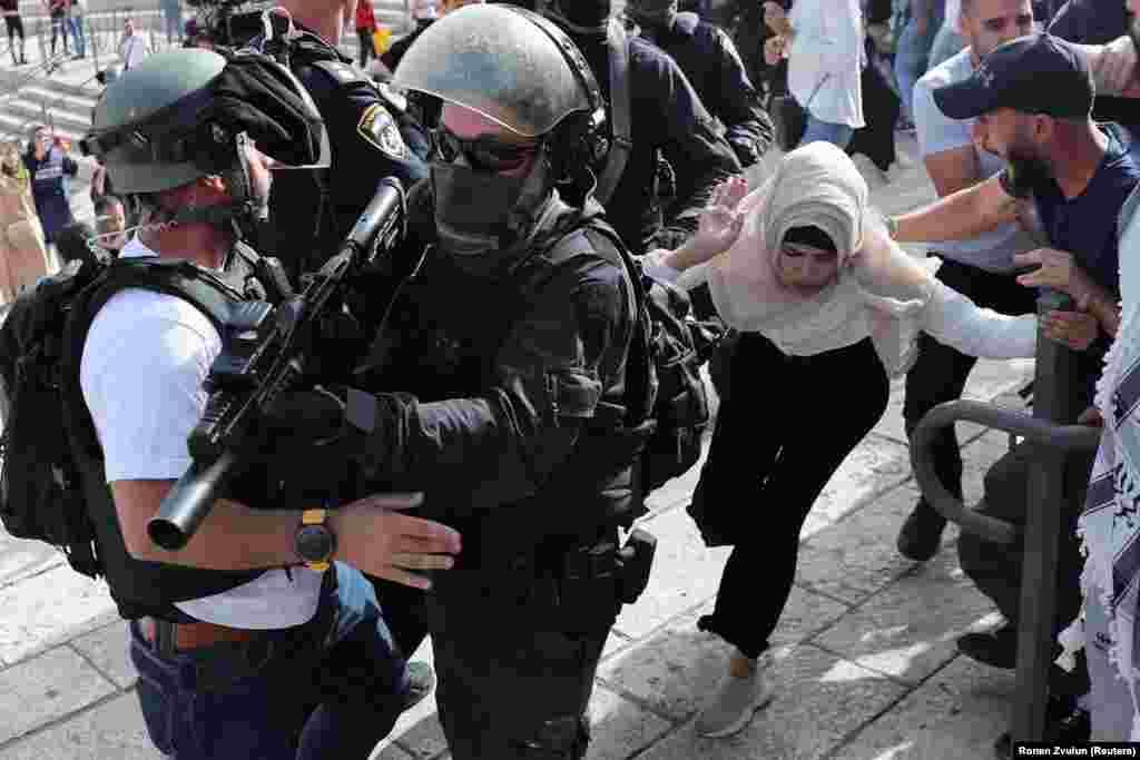 Палестинка біжить біля ізраїльських силовиків під час сутичок на тлі ізраїльсько-палестинської напруженості, коли Ізраїль відзначає День Єрусалиму біля Дамаських воріт біля Старого міста Єрусалиму, 10 травня 2021 року