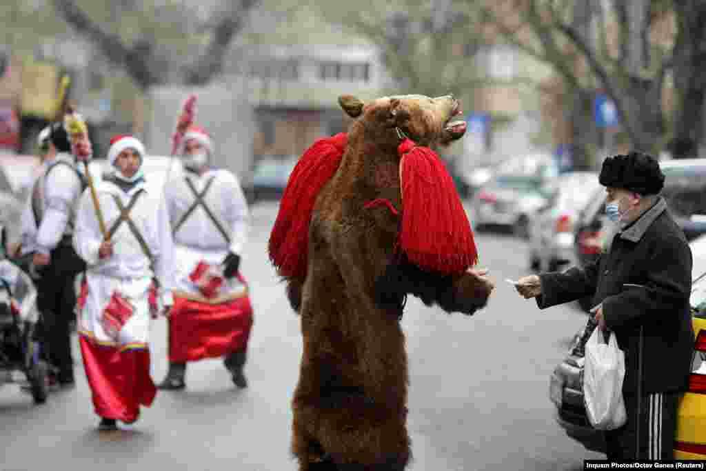 Уличный артист в костюме медведя собирает пожертвования после исполнения танца, «предсказывающего наступление Нового года» в центре Бухареста, Румыния. (Reuters/Октав Ганеа)