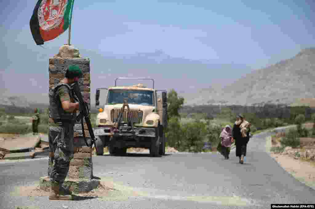An Afghan soldier watches from a checkpoint in Laghman Province on July 8 after Afghanistan's security forces reportedly cleared the area of Taliban militants.