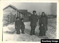 Copilărie în Siberia. Iarna anului 1956. Familia Ghieș, în fața casei lor din bârne: Vasile, Maria și fiii lor: Teodor, Victor și Grigore, născuți în locul de deportare