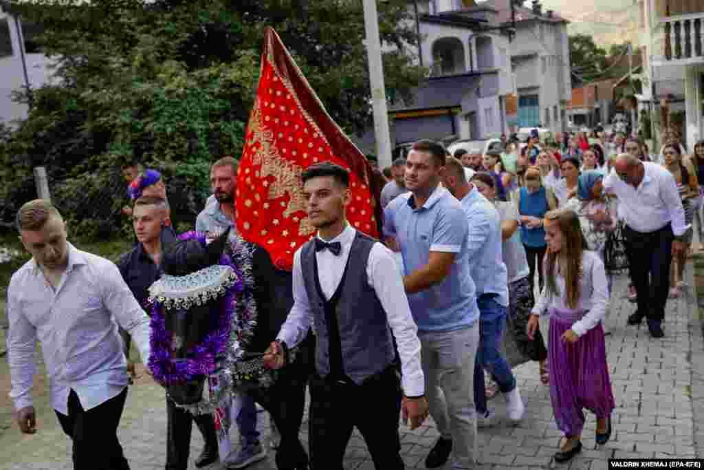 Мужчины ведут лошадь, на которой сидит невеста под красной накидкой. Свадебная процессия движется по улицам деревни