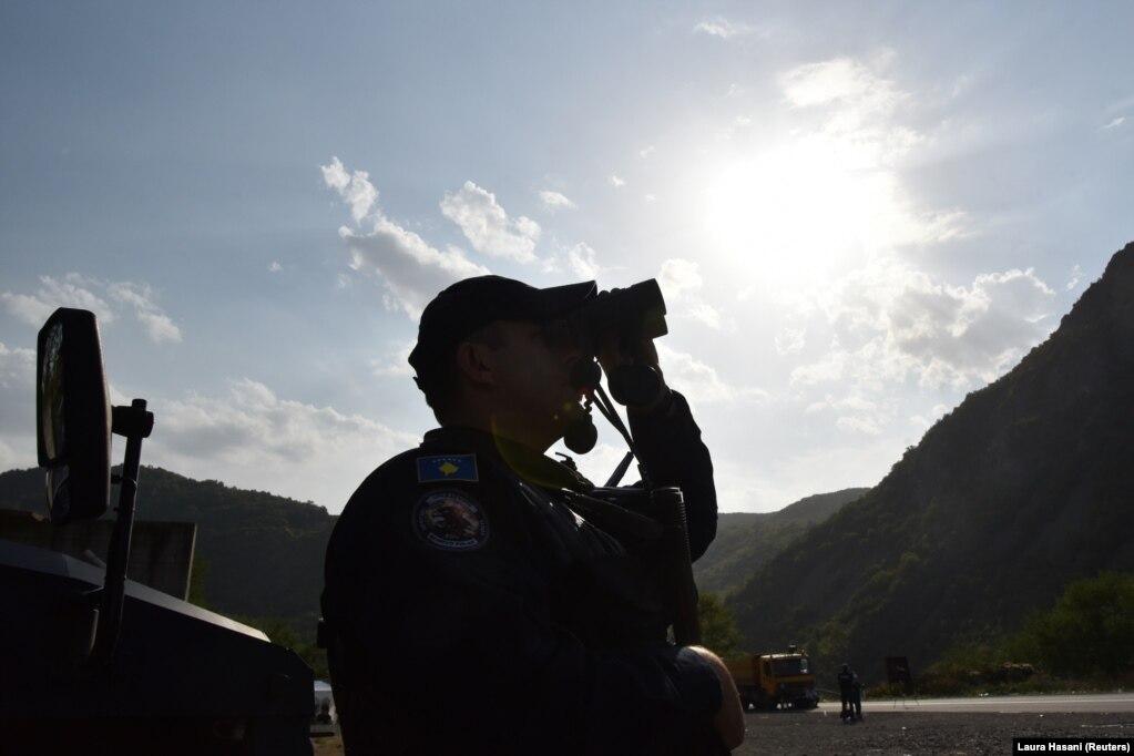 Një pjesëtar i njësitit special të Policisë së Kosovës duke vëzhguar me dylbi, në Jarinjë, në veriun e Kosovës. (27 shtator 2021)