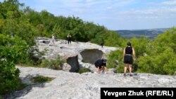 Туристки карабкаются по гладким скалам