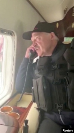 Lukashenka talks on the phone onboard a helicopter during his flight over Minsk on August 23.