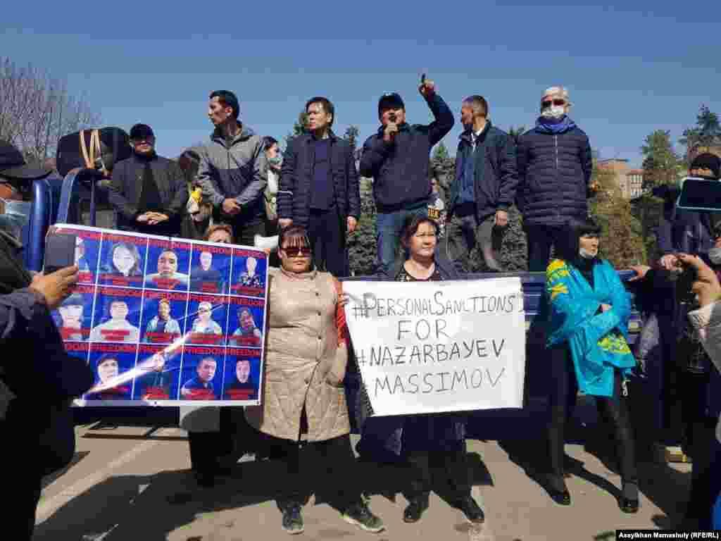 """Жиналғандар арасында """"Демпартия"""" өкілдерімен қатар ҚДТ жақтастары да болды. Олар митинг кезінде бірінші президент Нұрсұлтан Назарбаевқа санкция салуды, саяси тұтқындарды босатуды талап етіп, плакат ұстап тұрды."""