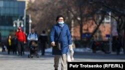 Женщина в защитной маске идет по улице в Алматы. 18 марта 2021 года.