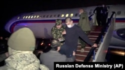 An Armenian prisoner is escorted off a Russian military plane upon arrival at a military airport outside Yerevan, Armenia, in December 2020