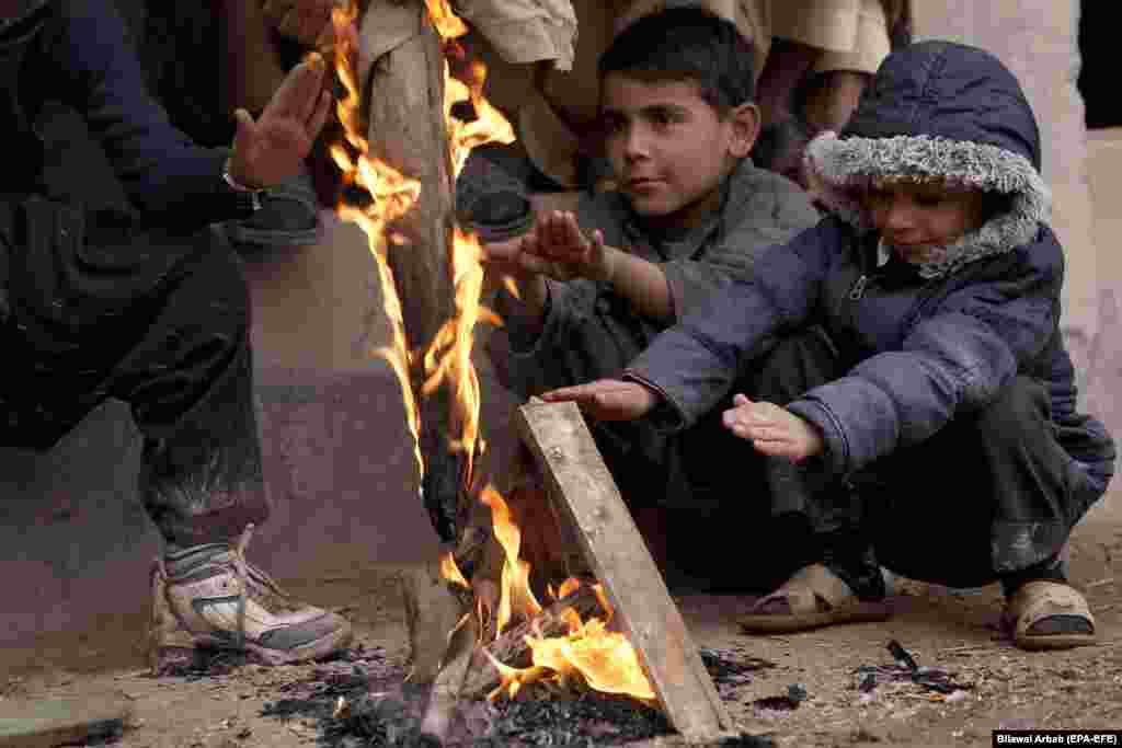 Children warm themselves around a fire to beat the cold on a roadside in Peshawar, Pakistan. (epa-EFE/Bilawal Arbab)