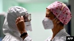 Egy munkatársa segít egy nővérnek, hogy felvegye a védőfelszerelését a San Filippo Neri kórház koronavírusos betegek számára kialakított intenzívosztályán Rómában, 2020. október 29-én.