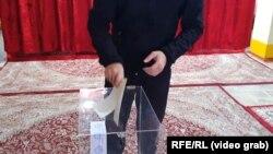 Сайлау жәшігіне бірден артық бюллетень салып тұрған сайлаушы. Душанбе, 11 қазан 2020 жыл.