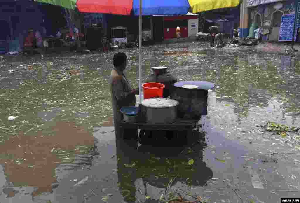 A food vendor waits for customers in a flooded area after heavy monsoon rains in Lahore, Pakistan. (AFP/Arif Ali)