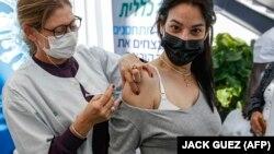 Egészségügyi alkalmazott beadja a Pfizer/BioNTech-vakcinát egy terhes nőnek Tel-Avivban, 2021. január 23-án