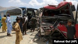 People stand near damaged buses after a deadly accident on the Kabul-Kandahar highway on April 27.