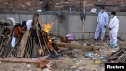 Dva člana porodice stoje pored lomače koja odnosi tjelo njihovog rođaka preiminulog od posledica infekcije korona virusom u glavnom gradu Indije Nju Delhiju. 22. spril 2021.