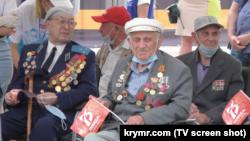 Участник Второй мировой войны, крымский партизан Куддус Юнусов (в центре) наблюдает за военным парадом. Симферополь, 24 июня 2020 года