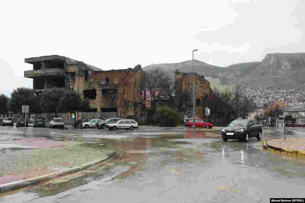 """Zgrada među Mostarcima poznatija kao """"Jagnje"""", na Španskom trgu; gdje se u vrijeme prije rata nalazio istoimeni restoran; riječ je o nizu objekata izgrađenih takođe u vrijeme austrougarske uprave u BiH; u istom redu objekata, na suprotnom kraju, nalazi se velika ruševina u kojoj je bilo sjedište tadašnje Ljubljanske banke u Mostaru, koja je takođe izgrađena u vrijeme SFRJ (Socijalistička Federatinva Repulika Jugoslavija)."""