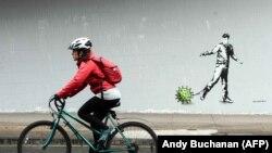 Egy kerékpáros elhalad egy koronavírus által inspirált graffiti mellett Glasgow-ban, 2020. április 4-én