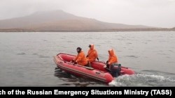 Russian Emergency Situations Ministry workers take water samples from waters by the village of Zavoiko on October 6.
