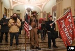 """Donald Trump támogatói, köztük közepén a """"Q Sámán"""", a Capitoliumban, miután áttörték a védelmi intézkedéseket és bejutottak az épületbe, 2021. január 6-án."""