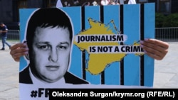 Kateryna Yesypenko holds a poster calling for her husband to be freed.