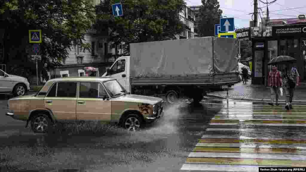 Старенький ВАЗ тормозит, поднимая брызги, перед пешеходным переходом