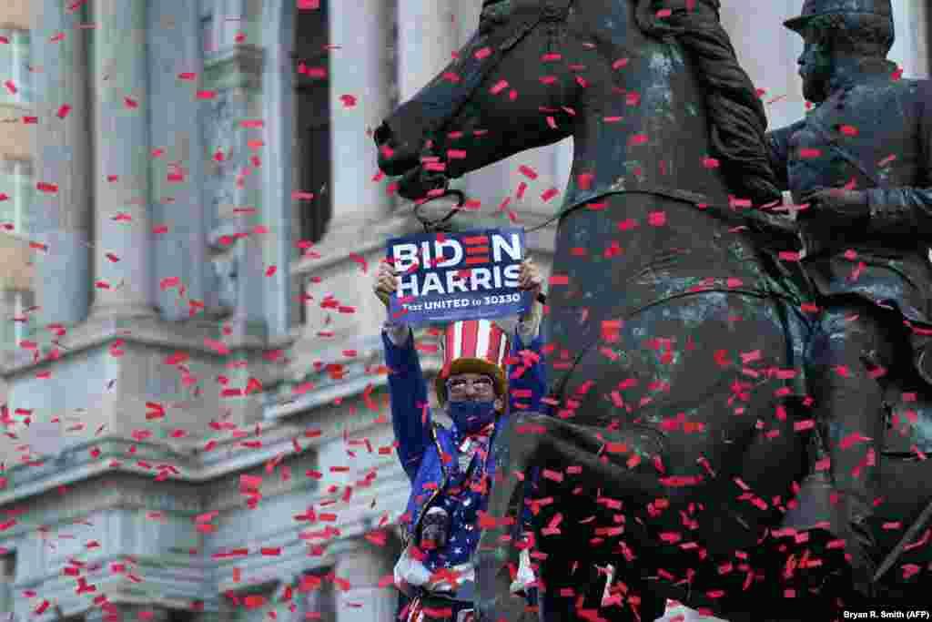 Чоловік, одягнений як Дядько Сем, святкує, стоячи на статуї, після того, як ЗМІ оголосили Джо Байдена наступним президентом США, Філадельфія