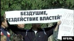 Участник забастовки торговцев базара держит плакат с критикой властей. Петропавловск, 30 июля 2009 года.