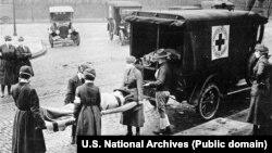 США, місто Сент-Луїс у штаті Міссурі, 1918 рік. Представники Червоного Хреста у масках винесли з будинку для подальшого транспортування жертву іспанського грипу (іспанки)