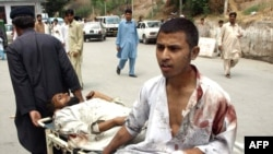 A man pulls a stretcher carrying bomb blast victims outside a hospital in Peshawar.