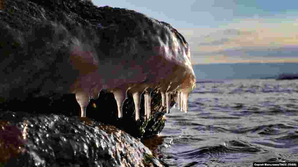 Наледь на камнях на берегу Черного моря в Феодосии