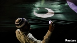 A supporter of the religious party Jamaat-e Islami takes pictures with a mobile phone as he holds Pakistan's national flag during an election campaign rally in Karachi.