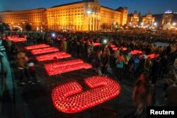 "People light candles at Independence Square in Kyiv to form the words ""Glory to Ukraine, glory to the Heroes!"" during a rally to show support for servicemen on the front line in eastern Ukraine in 2014."