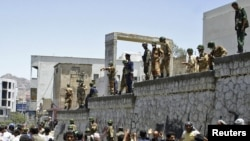 Soldiers and police stand guard during clashes between antigovernment protesters and supporters of Yemeni President Ali Abdullah Saleh in the southern city of Taiz on April 5.
