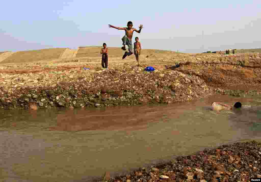 An Afghan boy jumps into muddy water as he goes for a swim with friends on the outskirts of Jalalabad. (Reuters/Parwiz)