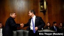 Директор ФБР Кристофер Рэй (справа) обменивается рукопожатием с сенатором Линдси Грэмом перед началом слушаний в Сенате