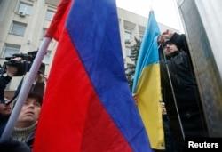 Люди заменяют украинский флаг на российский во время пророссийской акции в Симферополе, 27 февраля 2014 года