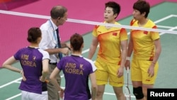 An official speaks to players from China and South Korea during their women's doubles badminton group match on July 31.